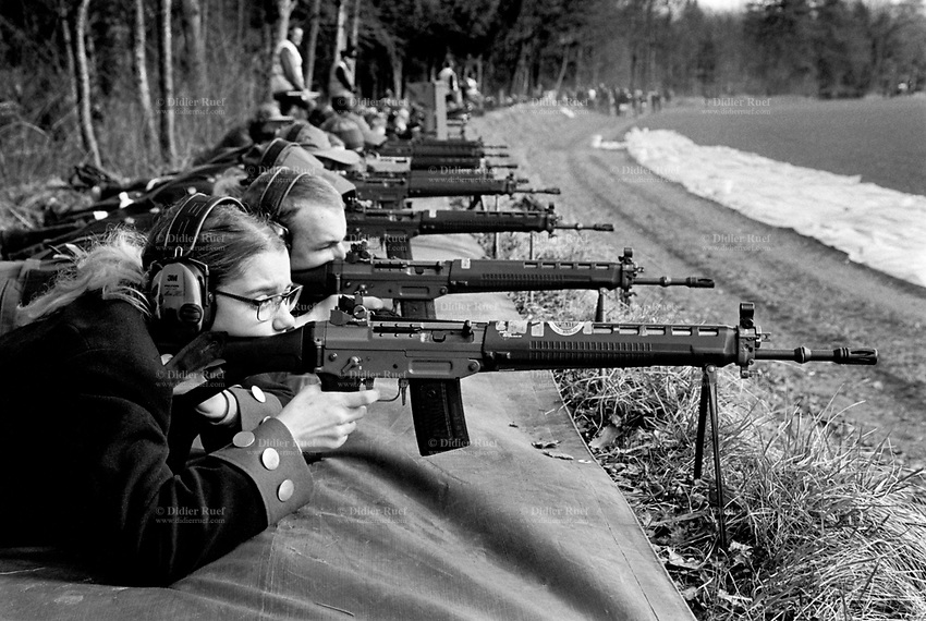"""Switzerland. Canton Bern. Neuenegg. Historisches Neueneggschiessen. A group of men and a woman are firing with automatic or semi-automatic assault rifles SG 550 during the traditional firing tournament for the Neuenegg battle's celebration. On March 5, 1798, under the command of Colonel Johann Rudolf von Graffenried, the Bernese army triumphed over numerically superior French troops under Brigadier General Pigeon. The Swiss proved their military skills by defeating a Napoleonic brigade. Napoleon still conquered Switzerland, but that hasn't prevented the celebration of Neuenegg's victory each year. The SG 550 is an assault rifle manufactured by Swiss Arms AG (formerly a division of Schweizerische Industrie Gesellschaft now known as Sig Holding AG) of Neuhausen, Switzerland. """"SG"""" is an abbreviation for Sturmgewehr, or """"assault rifle"""". The rifle is based on the earlier 5.56mm SG 540 and is also known as the Fass 90 (Fusil d'assaut 90/Fucile d'assalto 90) in French/Italian or Stgw 90 in German (Sturmgewehr 90). 5.03.2017 © 2017 Didier Ruef"""