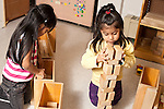 Education preschool 3-4 year olds two girls building with blocks near each other but playing separately