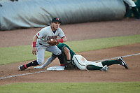 Matt Gorski (36) of the Greensboro Grasshoppers slides head first into third base ahead of the tag by Frainyer Chavez (5) of the Hickory Crawdads at First National Bank Field on May 6, 2021 in Greensboro, North Carolina. (Brian Westerholt/Four Seam Images)