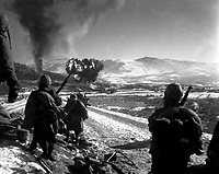U.S. Marines move forward after effective close-air support flushes out the enemy from their hillside entrenchments.  Billows of smoke rise skyward from the target area.  Hagaru-ri.  December 26, 1950.  Cpl. McDonald.  (Marine Corps)<br /> NARA FILE #:  127-N-A5439<br /> WAR & CONFLICT BOOK #:  1432