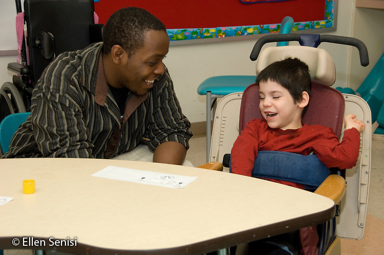 MR / Albany, NY.Langan School at Center for Disability Services .Ungraded private school which serves individuals with multiple disabilities.Teaching assistant (African-American) and child in Rifton chair laugh as they interact. Boy: 8, cerebral palsy, spastic quadriplegic, nonverbal with expressive and receptive language delays.MR:  Hac2; Wes2.© Ellen B. Senisi