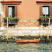 A small wooden rowing boat moored on a canal in Venice, Italy