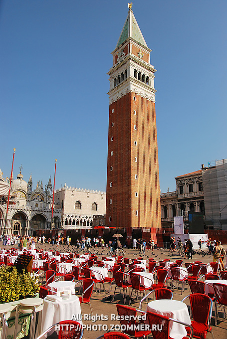 St Mark's Campanile on St Marco Square, Venice. Cafe tables in front.