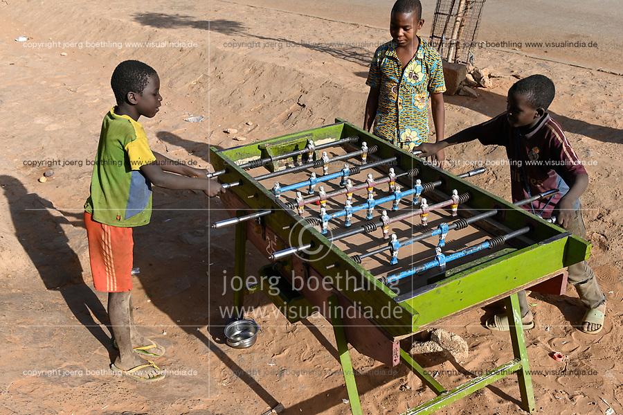NIGER, Niamey, Talibé boys, children belong to a quranic school daara, play table football during their begging tour / NIGER, Niamey, junge Koranschueler einer Koranschule spielen am Fußball Kickertisch waehrend ihres Bettelgangs
