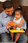 14 month old toddler girl with father playing with puzzle father holding up piece and naming animal