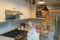 Off duty US soldier in uniform at home in his kitchen,  banking and paying bills, for sale as stock photography