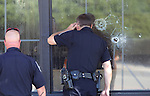 Officers look past bullet holes into an IHop restaurant in Carson City, Nev., on Tuesday, Sept. 6, 2011, following a shooting that reportedly has left eight wounded and four dead. (AP Photo/Cathleen Allison)