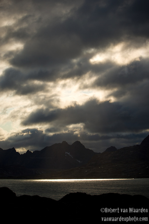 The sun breaks through the clouds of Eastern Greenland, illuminating the mountains and landscape.