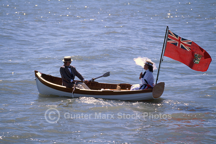 Gentleman and Lady in Historic Period Costume rowing in Rowboat with Historical Red Ensign Flag flying behind - Afternoon Boat Ride