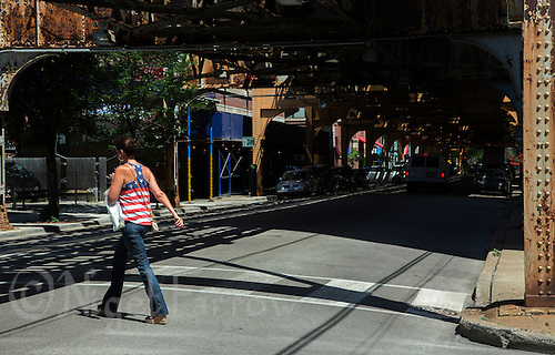 01 JUL 2014 - CHICAGO, USA - A pedestrian dressed in a Stars and Stripes top crosses the road under the tracks of the elevated train system, The L, at the North Franklin Street and West Huron Street junction in Chicago in the USA (PHOTO COPYRIGHT © 2014 NIGEL FARROW, ALL RIGHTS RESERVED)