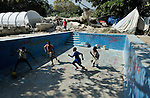 Children play soccer in what was once the swimming pool of the Italian Embassy in Port au Prince, Haiti. Destroyed by the January 12, 2010, earthquake, the building is now a source of rebar and other salvaged building materials for enterprising recyclers, and the pool a convenient playground for children who live in the Narret Camp for homeless quake survivors, which surrounds the rubble. Residents of the camp have been assisted by the Lutheran World Federation, a member of the ACT Alliance.