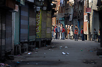 People watch from a side street as paramilitary police enforce a curfew imposed to stop separists gather for a political demonstration in Srinagar, Kashmir, India.  Fredrik Naumann/Felix Features