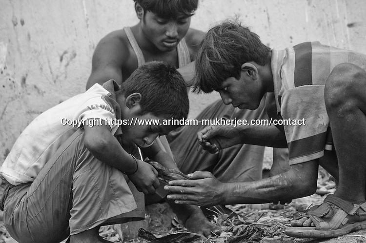 Children do brown sugar at the sealdah parking zone in Kolkata, India.
