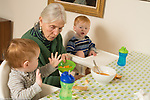 20 month old toddler fraternal twin boys with grandmother, meal time. Child care she takes care of them twice a week