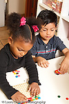 Education preschool 3-4 year olds two children playing side by side girl playing with manipulative toy boy playing with toy car vertical