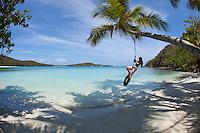 Alexander Krasny on a tire swing at  Gibney / Oppenheimer Beach.Virgin Islands National Park.St. John, U.S. Virgin Islands