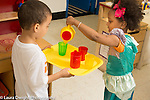 Education preschool 3 year olds pretend play boy holding tray with cups on it that girl is filling from teapot, using left hand
