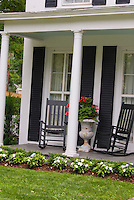 Two rocking chairs on classic front open porch of old Colonial style house, lawn grass, pretty flowers, planter