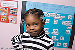 Education Preschool 3-4 year olds portrait of girl smiling board of class names on wall behind her horizontal