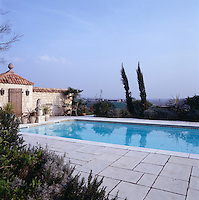The stone-built poolhouse at one end of the new swimming pool acts as a windbreak and has old roof tiles and a rustic door