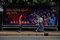 A woman carrying a traditional lunch box walk beside an ORODOO mobile phone network advertising, <br /> Yangon on a sunny day of July 2017