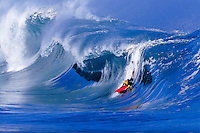 Bodyboarding on the big waves at beautiful Waimea Bay, on the north shore of Oahu.