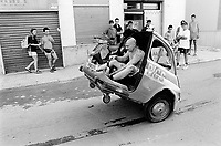 """Italy. Province of Sicily. Menfi. Mutoid Waste Company. A man drives and tests the Fiat 250 (a Fiat 500 cuts in half) before the start of the show at """"Inycon"""" festival. Using all types of industrial scrap for their raw materials the Mutoid Waste Company are a mobile and adaptable group of performance artists. Having the necessary equipment to allow them complete freedom, they have created an entirely new form of scultural-musical performance crossing the boundaries of circus, theatre and art.  © 1999 Didier Ruef"""