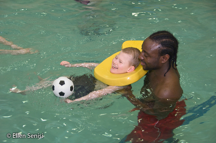MR / Albany, NY.Langan School at Center for Disability Services .Ungraded private school which serves individuals with multiple disabilities.Teaching assistant (African-American) holds non ambulatory student using head float in pool during gym class. Students in this class swim once a week as part of their physical education program. Boy: 9, cerebral palsy, non verbal with expressive and receptive language delays.MR: Law4; Gen1.© Ellen B. Senisi