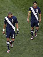 Oguchi Onyewu (L) and Carlos Bocanegra (R) of USA walk off dejected at half time against Slovenia