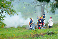 British artillery unit fires a field cannon at the Continental Army while defending the Fort during a Revolutionary War re-enactment at Fort Ticonderoga, New York, USA.