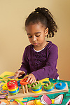 Four year old girl playing with number sorting puzzle putting pieces on pegs by number of holes in each piece colored wooden toy