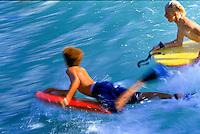 Two boys bodyboarding at 'The Wall', Waikiki, Oahu.