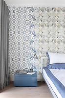 An unusual wallpaper with a pattern that resembles overlapping stencilling has been used for one of the bedroom walls