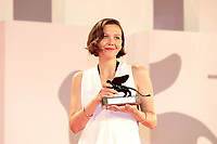 """VENICE, ITALY - SEPTEMBER 11: Maggie Gyllenhaal poses with the Award for Best Screenplay for """"The Lost Daughter"""" at the awards winner photocall during the 78th Venice International Film Festival on September 11, 2021 in Venice, Italy."""