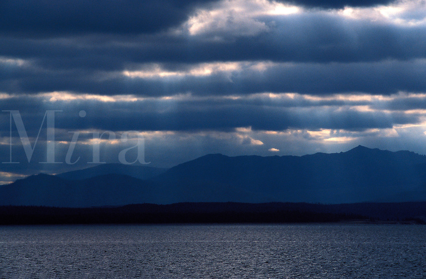 Sunlight filters through clouds to water.