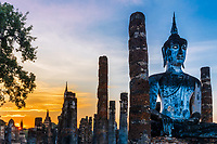 Wat Maha That temple, lit-up Buddha statue at sunset with sunrays and a beautiful orange sky, in the famous Sukhothai Historical Park, Thailand