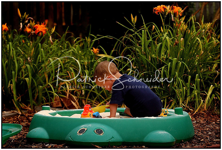 A young boy plays in a turtle-shaped sandbox in the backyard. Image is model released.