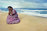 Mother who lost her three children to the sea when the tsunami hit   <br /> Batticola, Sri Lanka 2005.<br /> Of the 8,000 residents of Batticaloa, 5,000 died. That's 60 percent of its population. The once-thriving beach-front village was surrounded by a lagoon so there was nowhere to run when the giant wave hit, just into more water. Saris and clothing were left embedded in the barbed wire set up to protect against wild animals, where many of the bodies were trapped in its grip. A few remnants were scattered: cooking pots, photographs with cracked glass, clocks stopped when the wave hit at 9:22, Buddhist statues which mysteriously remained standing. But mostly there was just rubble. Everywhere had its own ghosts. <br /> I viewed the beach, cluttered with personal effects. Human bones had started to wash up. A woman walked alongside me who appeared to be in shock. As I turned to ask if she was all right she began madly gesticulating toward the sea, indicating that it had taken her two children. She, as so many I encountered, now lived with the image of seeing her family swept away and struggled with the profound guilt of being unable to hold onto her children. Beside herself with anguish she attempted to throw herself into the ocean. I pulled her back and held her as she wept. Inconsolable, she buried her face in the sand. Death is certainly more integrated with life in this part of the world, but there was no quantifying the universality of a mother's pain.