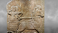 Hittite relief sculpted orthostat stone panel of Long Wall Limestone, Karkamıs, (Kargamıs), Carchemish (Karkemish), 900 - 700 B.C. Anatolian Civilisations Museum, Ankara, Turkey<br /> <br /> Chariot. One of the two figures in the chariot holds the horse's headstall while the other throws arrows. There is a naked enemy with an arrow in his hip lying face down under the horse's feet It is thought that this figure is depicted smaller than the other figures since it is an enemy soldier. The lower part of the orthostat is decorated with braiding motifs. <br /> <br /> On a grey art background.