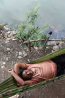 A man sleeps by a lake in central Jakarta. Nearly 40% of the city is below sea-level and many public areas often flood, even during the dry season.