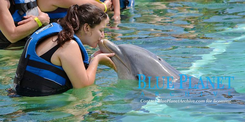 Girl kisses a bottlenose dolphin, Tursiops truncatus, at Sea Life Park, Oahu, Hawaii, USA