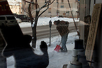 (name) shovels snow outside of Chicks From The Sticks antique and salvage store in Punxsutawney, PA.