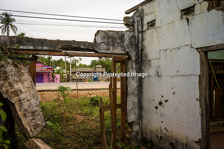 Policemen ride past the bullet ridden walls of the abandoned house by the side of the road where the last battle between the LTTE and the Sri Lankan army was fought, along the highway in Kilinochchi, in northern Sri Lanka. Photo: Sanjit Das/Panos