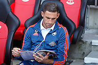 Angel Rangel reads the program on the bench before the Barclays Premier League match between Southampton v Swansea City played at St Mary's Stadium, Southampton
