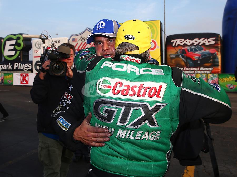 Feb 9, 2014; Pomona, CA, USA; NHRA funny car driver John Force (near) hugs Matt Hagan after winning the Winternationals at Auto Club Raceway at Pomona. Mandatory Credit: Mark J. Rebilas-