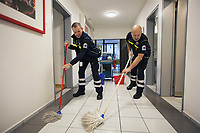 Switzerland. Canton Ticino. Pregassona. Headquarters of Croce Verde Lugano. Two paramedics are cleaning the corridor with mop on a Sunday morning. The reason is to make the environment sanitary and to remove allergens, in particular dust, stains, dirt and litter. Both men work for theCroce Verde Lugano and wear blue uniforms. Both are volunteers specifically trained in emergency rescue. TheCroce Verde Lugano is a private organization which ensure health safety by addressing different emergencies services and rescue services. Volunteering is generally considered an altruistic activity where an individual provides services for no financial or social gain to benefit another person, group or organization. Volunteering is also renowned for skill development and is often intended to promote goodness or to improve human quality of life. Pregassona is a quarter of the city of Lugano.14.01.2018 © 2018 Didier Ruef