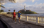 Salvador, Bahia State, Brazil. Lighthouse - Farol da Barra with a man and a woman running in the foreground.