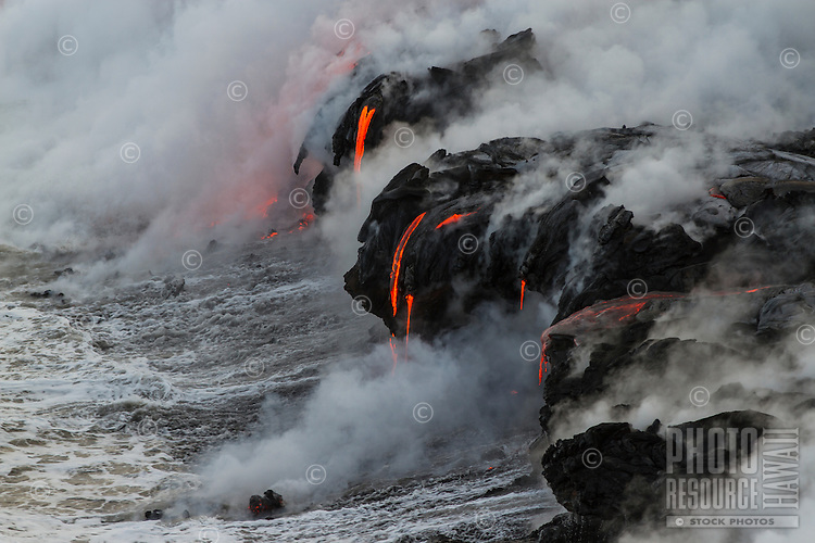 Extensive active lava tube flows along vast lava bench as boulders are vigorously swept out to sea, Hawai'i Volcanoes National Park and the Kalapana border, Big Island.