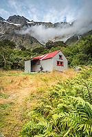 Tramper enjoying meal at Douglas Rock Hut in Copland Valley under Southern Alps, Westland National Park, West Coast, South Westland, World Heritage Area, New Zealand