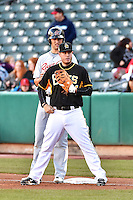 C.J. Cron (24) of the Salt Lake Bees holds the runner Nate Freiman (50) of the Sacramento River Cats during the game at Smith's Ballpark on April 5, 2014 in Salt Lake City, Utah.  (Stephen Smith/Four Seam Images)